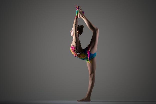 Menina do gymnast fazendo backbend de pé com mace