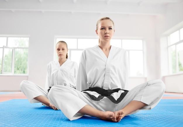 Menina do karaté de dois jovens que senta-se na posição de lótus após o treinamento no gym claro.