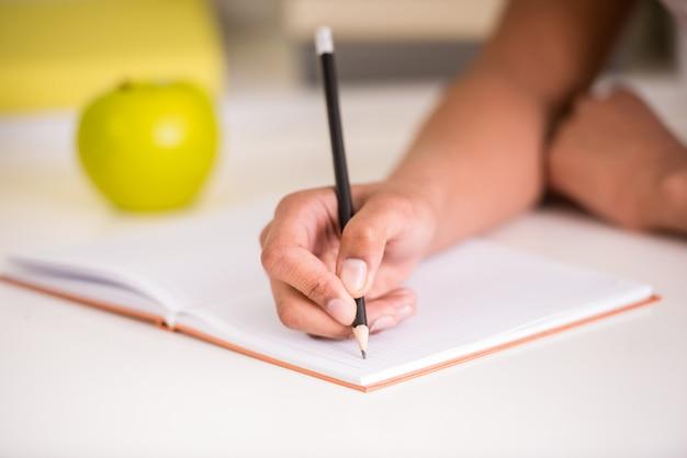 Menina do mulato que senta-se na tabela e que prende um lápis à disposicão.