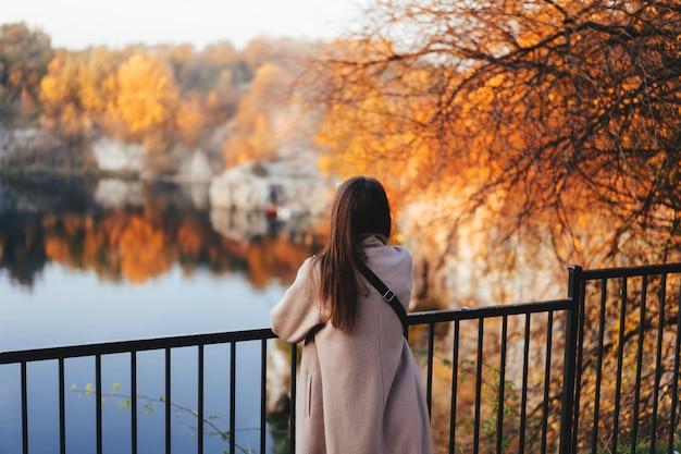 Menina do outono que está para trás e que olha a natureza.