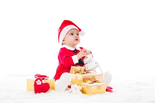 Menina do papai noel com caixa de presente e decorações de natal em uma pele