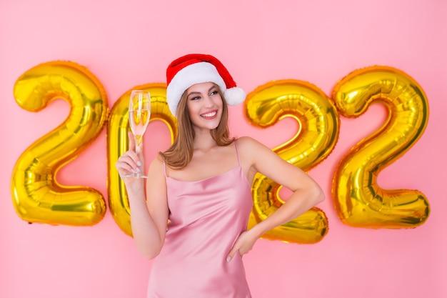 Menina do papai noel segurando uma taça de champanhe números dourados, balões de ar, conceito de ano novo