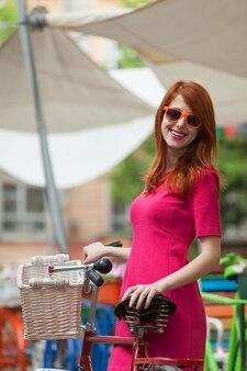 Menina do redhead com a bicicleta em ao ar livre, cidade.