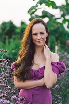 Menina do retrato com cabelo comprido em flores roxas. caminhe no jardim de flores. menina e flores. florística.