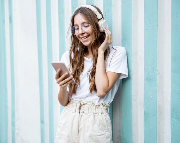 Menina do retrato com fones de ouvido e celular