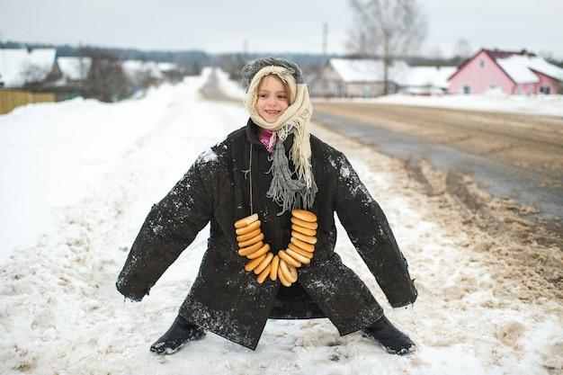 Menina do retrato com uma jaqueta grande e usada usando bagels no pescoço em um dia de inverno