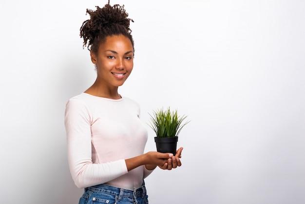 Menina do retrato da meia-volta com o potenciômetro da grama em suas mãos.