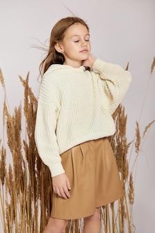 Menina do retrato da moda beleza na grama na primavera em um fundo branco. sorriso no rosto da menina