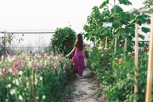 Menina do retrato de cabelo comprido com uma cesta de flores. caminhe no jardim de flores. menina e flores. florística.
