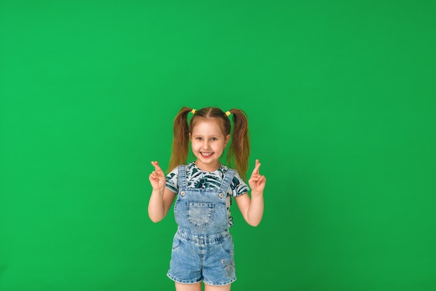Menina do retrato, dedos cruzados e desejando boa sorte, em um verde.