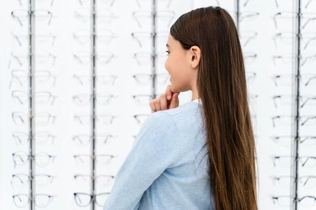 Menina do retrato na loja de óculos escolhendo um par