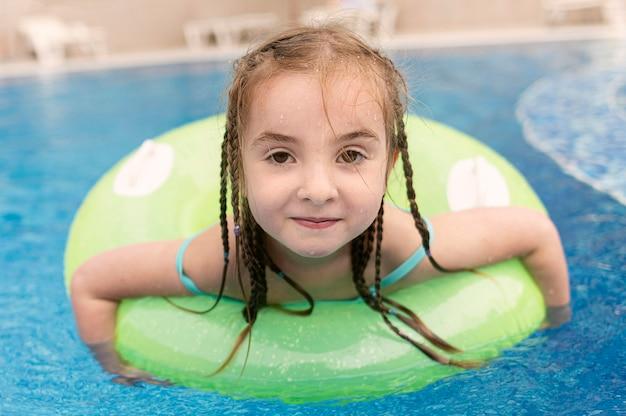 Menina do retrato no flutuador da piscina