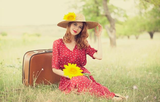 Menina do ruivo com o girassol em ao ar livre.