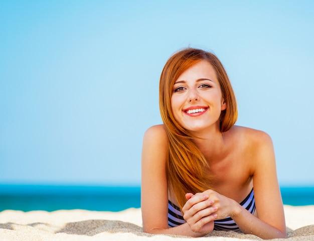 Menina do ruivo na praia no tempo de mola.
