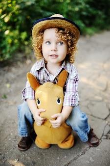 Menina do ruivo que monta um cavalo do brinquedo.