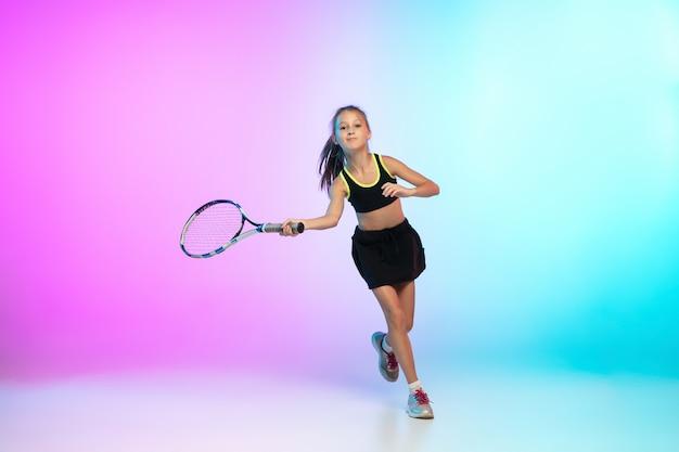 Menina do tênis em uma roupa esporte preta isolada em um fundo gradiente com luz de néon