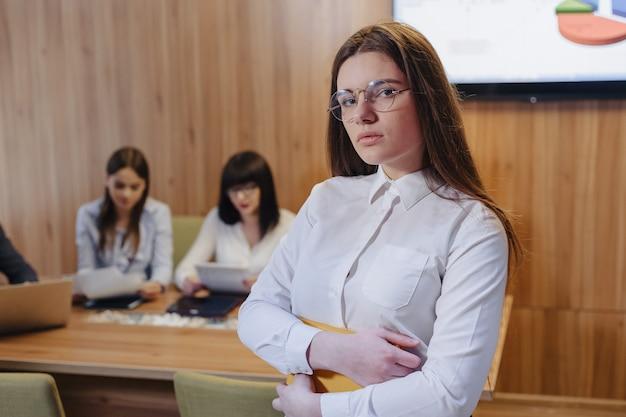 Menina do trabalhador de escritório elegante atraente jovem de óculos com um notebook nas mãos no fundo dos colegas de trabalho