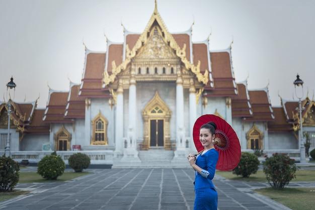 Menina do turista que aprecia no templo da esmeralda buddha, banguecoque, tailândia.
