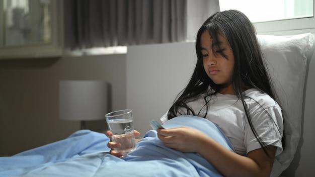 Menina doente, coberta por um cobertor, está deitada na cama e tomando uma pílula.