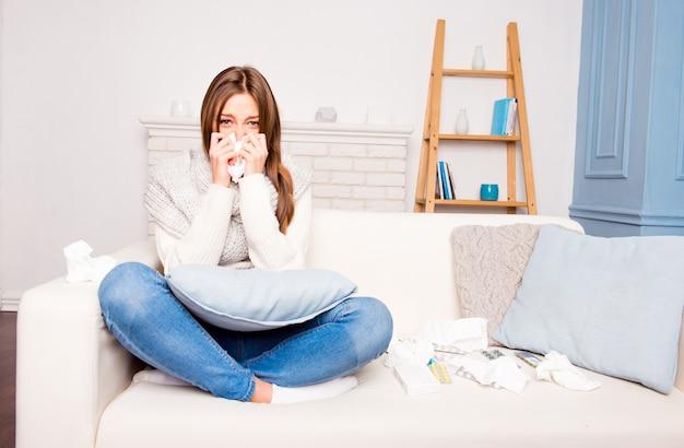 Menina doente com febre espirrando em um lenço de papel, sentada no sofá