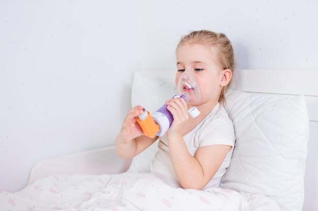 Menina doente com remédio para asma, deitada na cama. criança doente com inalador de câmara para tratamento da tosse. temporada de gripe. quarto ou quarto de hospital para paciente jovem. cuidados de saúde e medicamentos.