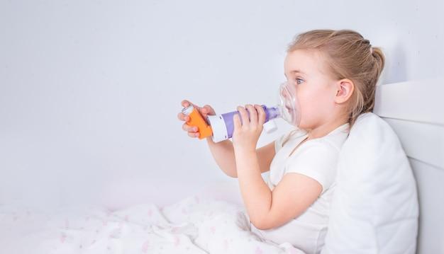 Menina doente com remédio para asma, deitada na cama. criança doente com inalador de câmara para tratamento da tosse