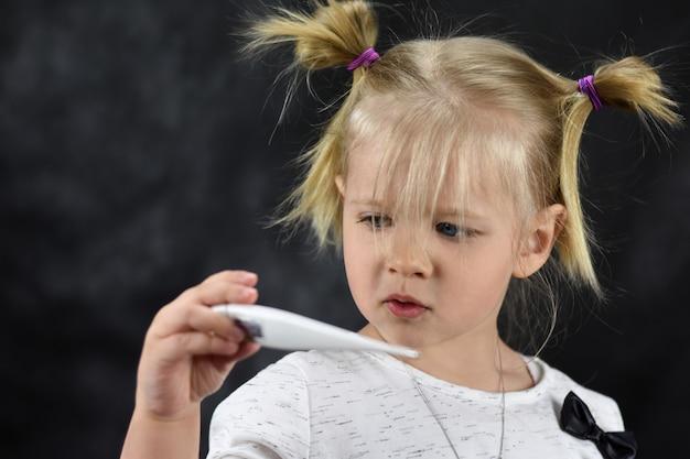 Menina doente criança olha para o termômetro na mão