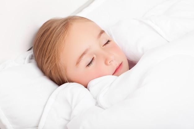Menina doente deitada na cama com um termômetro na boca