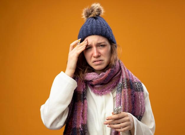 Menina doente e triste vestindo túnica branca e chapéu de inverno com lenço segurando uma seringa com pílulas colocando a mão na testa isolada na parede laranja