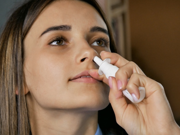 Menina doente enterra gotas de nariz closeup