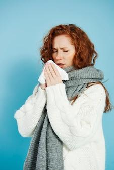 Menina doente espirrando e enxugando o nariz