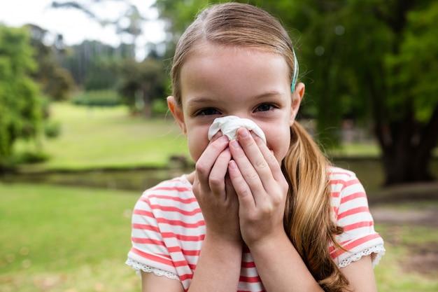 Menina doente, espirros no parque