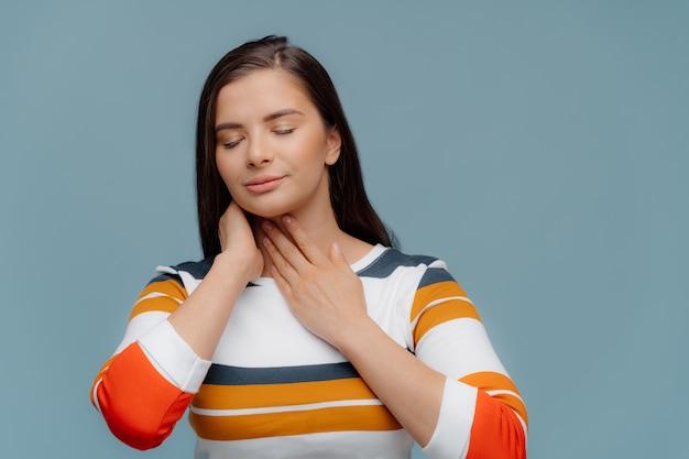 Menina doente insalubre toca garganta inflamada, sofre de dor