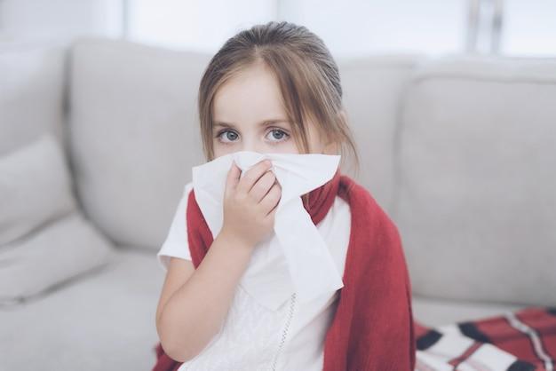 Menina doente se senta em um sofá branco envolto em um lenço vermelho
