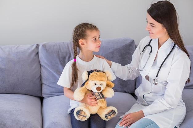 Menina doente sendo examinada pelo médico