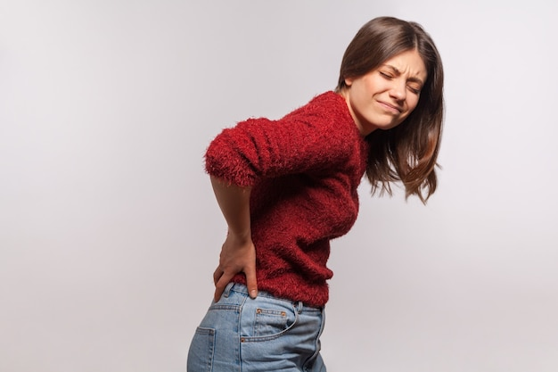 Menina doente tocando dor nas costas, sentindo dor aguda, sofrendo de inflamação nos rins