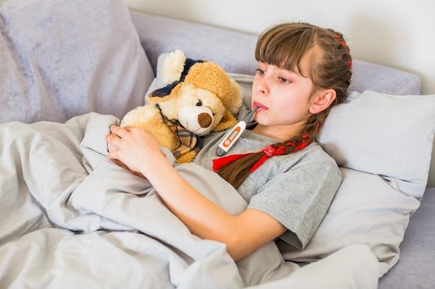 Menina doente usando termômetro