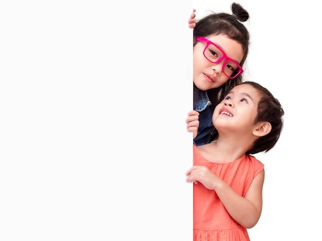 Menina dois bonito pequena feliz atrás de uma placa branca.