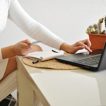Menina dona de casa em uma camisola branca aconchegante e meias em uma cadeira com um cobertor trabalha com um laptop na cozinha.