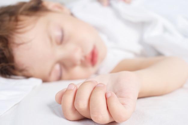 Menina dorme na cama. conceito de sono do bebê. foco seletivo.