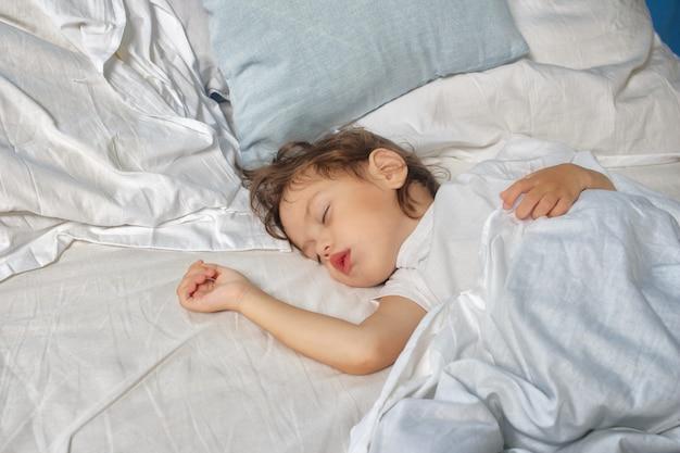 Menina dorme na cama. conceito de sono do bebê.