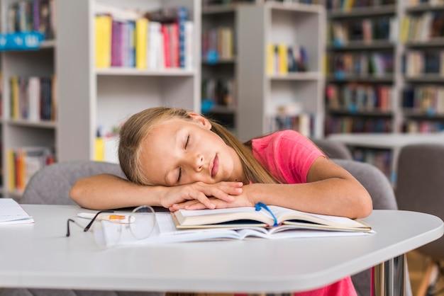 Menina dormindo em sua lição de casa na biblioteca
