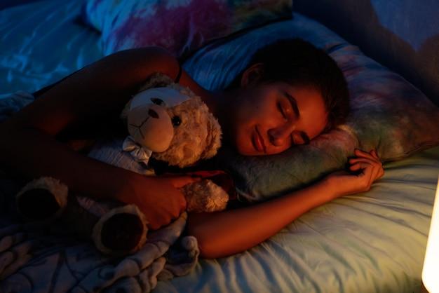 Menina dormindo em uma cama com um brinquedo macio, luz de uma luz noturna