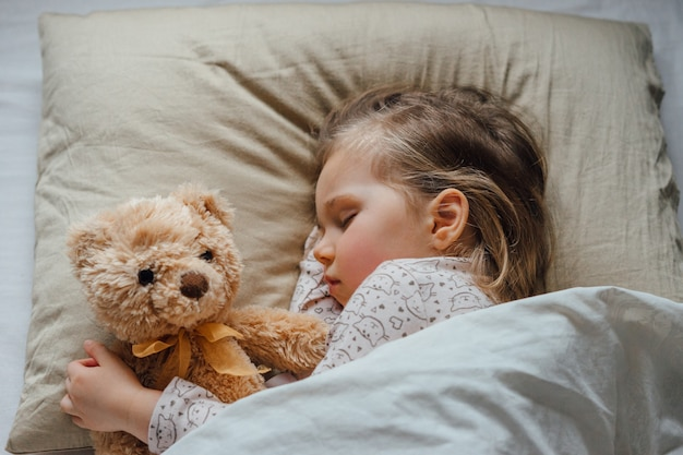 Menina dormindo na cama abraçando o brinquedo macio em casa, vista de cima