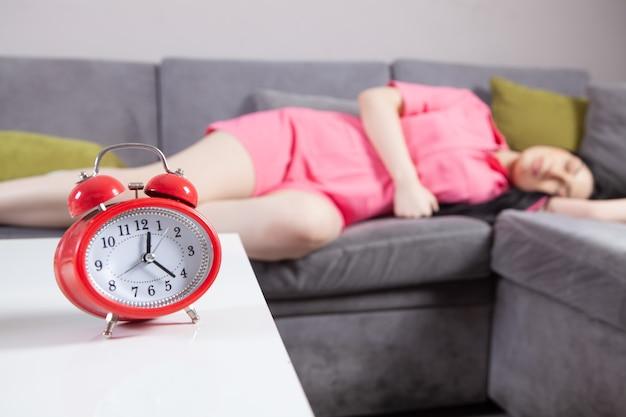 Menina dormindo na cama ajustando o despertador