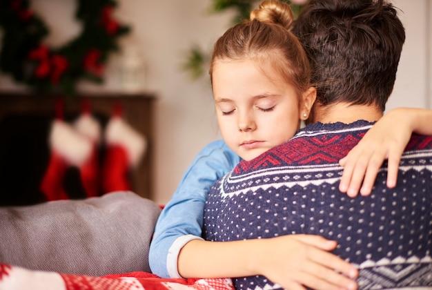 Menina dormindo nos braços do pai