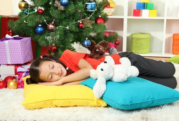 Menina dormindo perto da árvore de natal