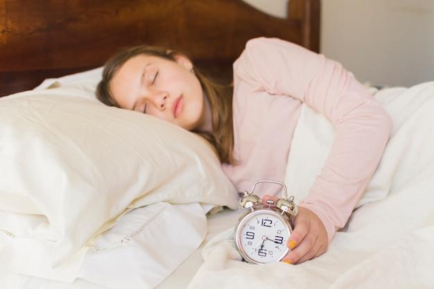 Menina, dormir, com, despertador, cama