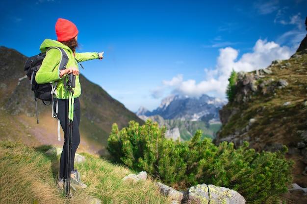 Menina durante uma caminhada alpina sinaliza um pico de montanha