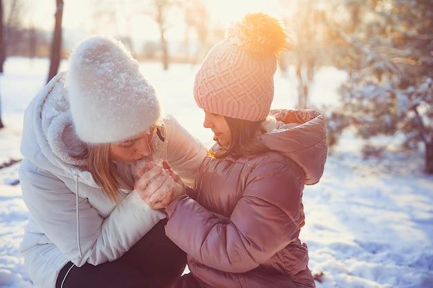 Menina e a mãe brincando ao ar livre no dia ensolarado de inverno